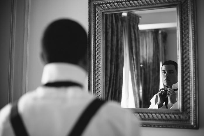 groom tying his bow tie
