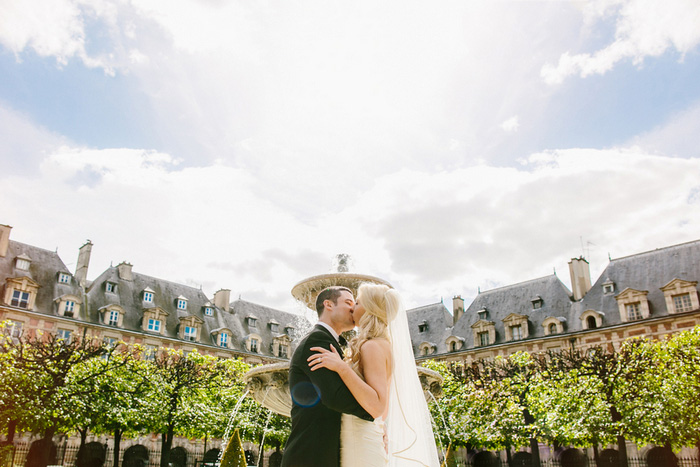 bride and groom kissing in front of fountain