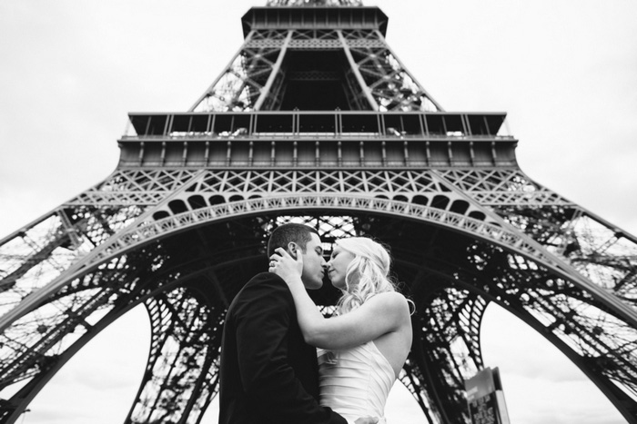 bride and groom under eiffel tower