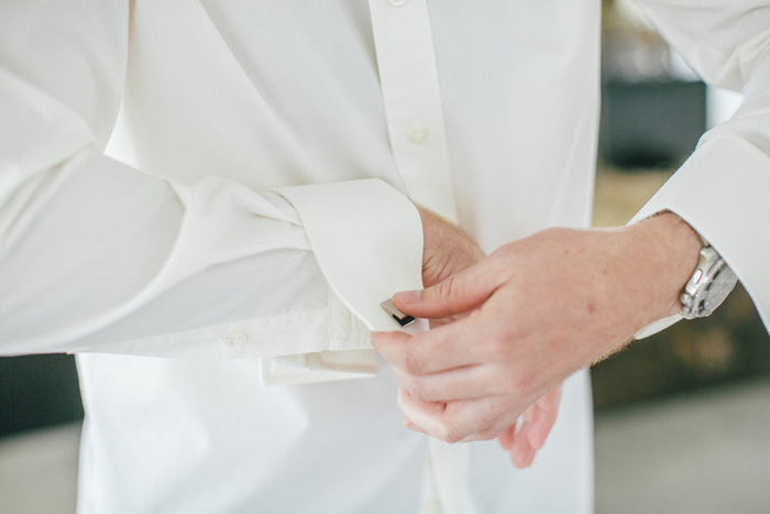 groom doing up cuffs