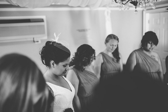 bride holding hands with bridesmaids praying