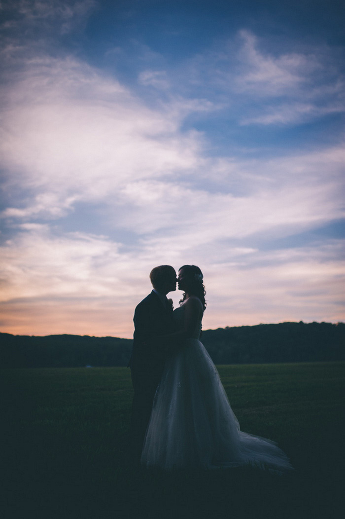 bride and groom kissing at dusk