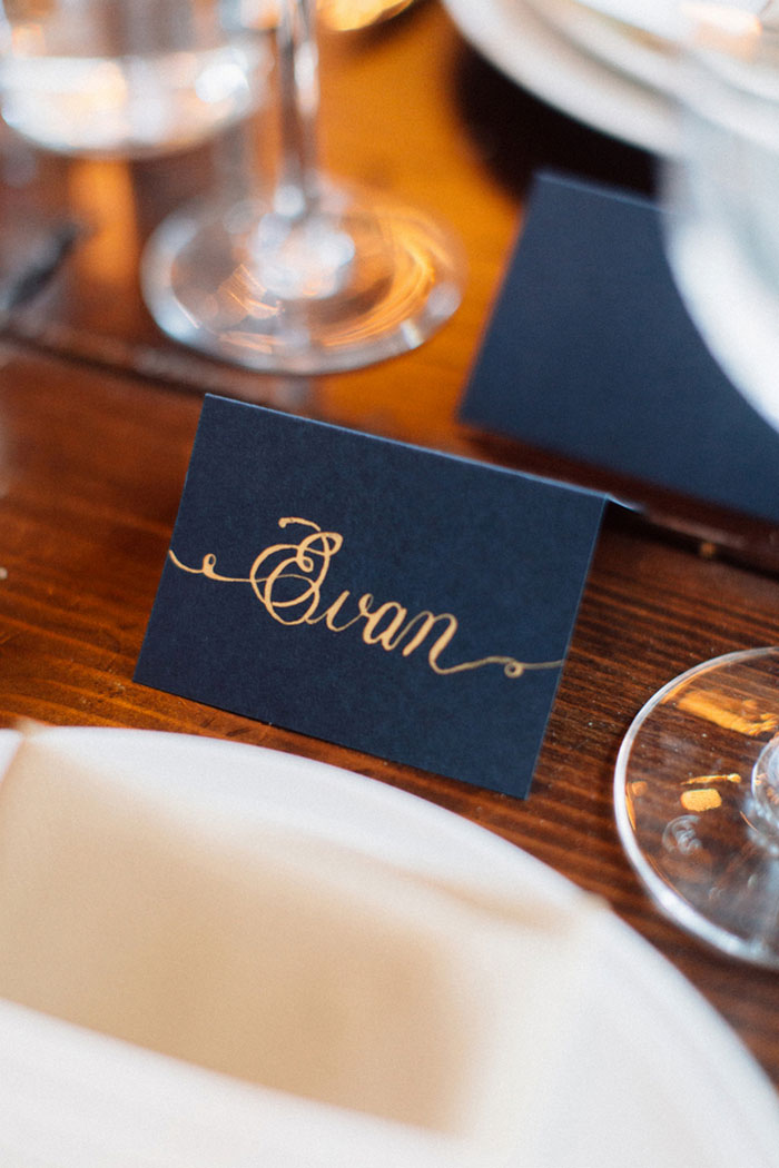 gold calligraphy on navy place cards