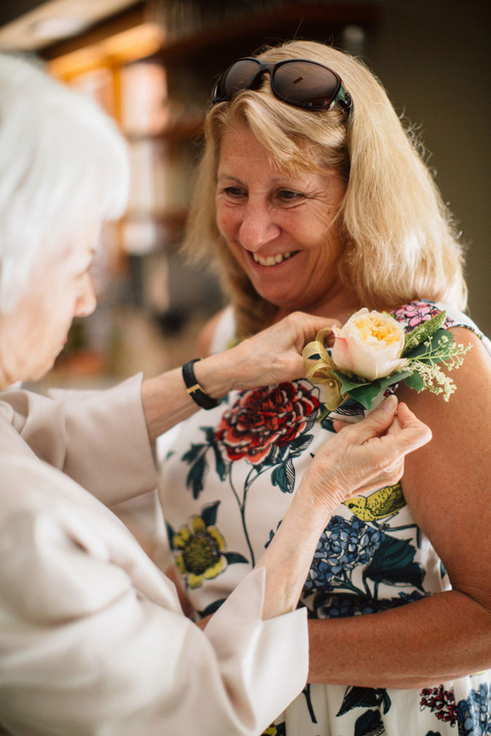 boutonniere being pinned on mother