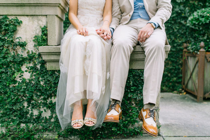bride and groom sitting on stone step