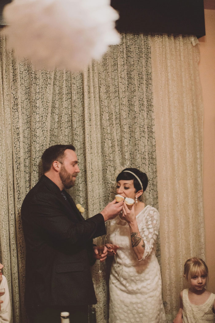groom feeding bride a cupcake