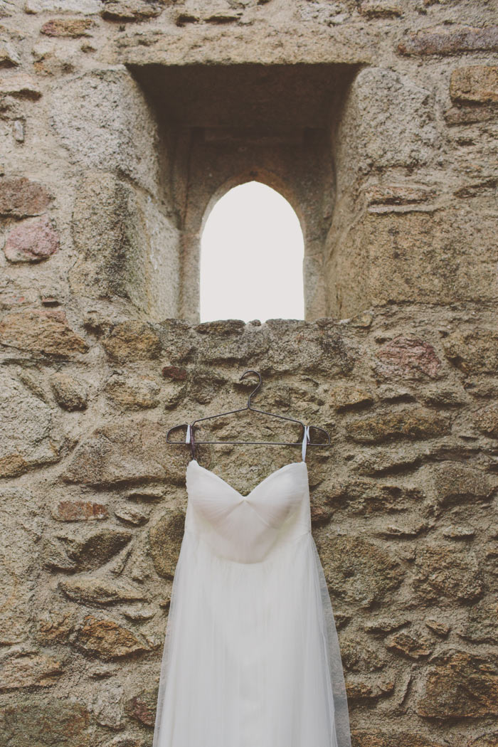wedding dress hanging on stone wall