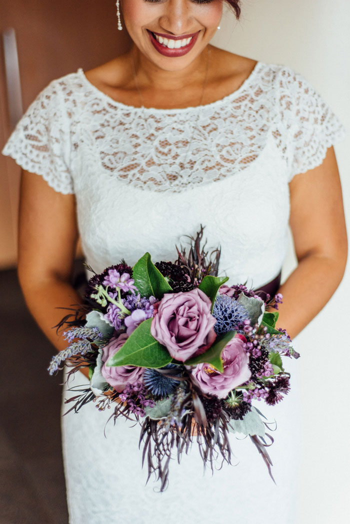 bride holding purple rose bouquet