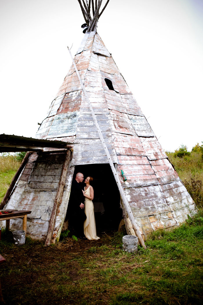 bride and groom portrait next to teepee