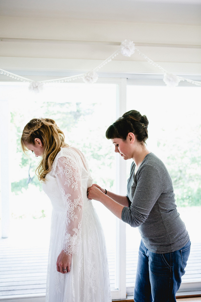 bride getting buttoned into dress