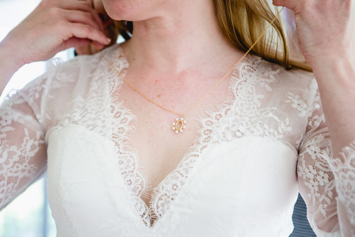 bride putting o n necklace