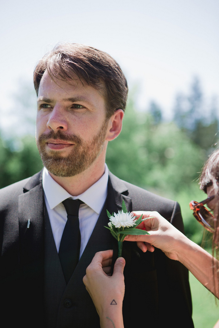 groom getting boutonniere pinned on