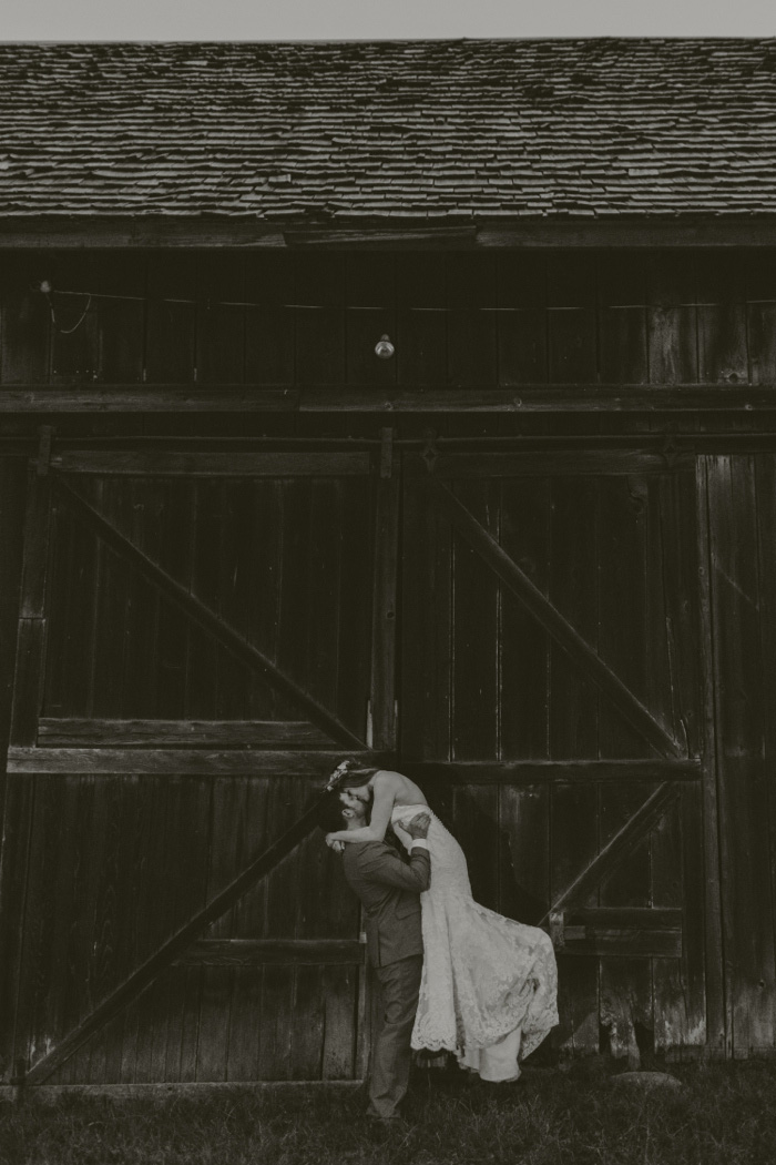 groom lifting bride up as he kisses her