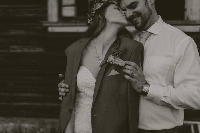 bride wearing groom's jacket and kissing him on the cheek