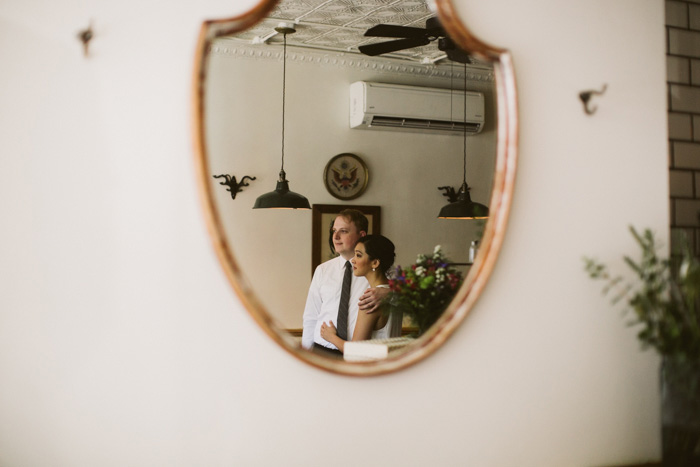 reflection of bride and groom in restaurant mirror