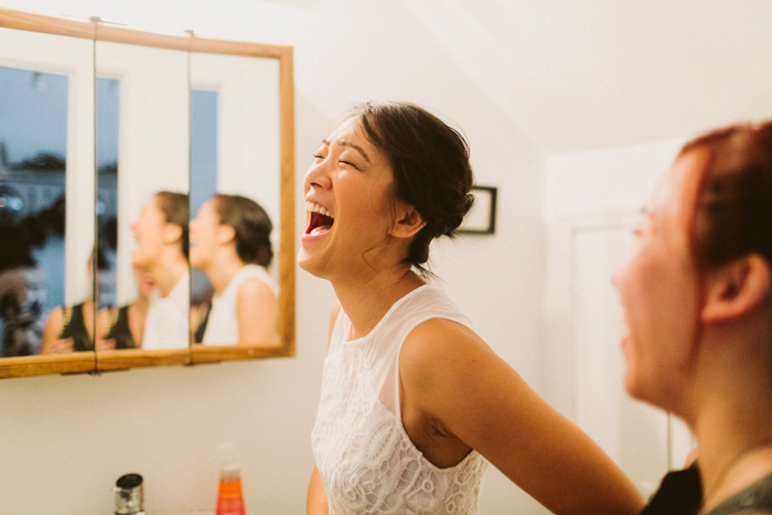 bride laughing while getting ready