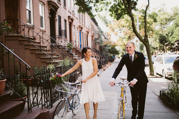bride and groom wheeling bikes down street
