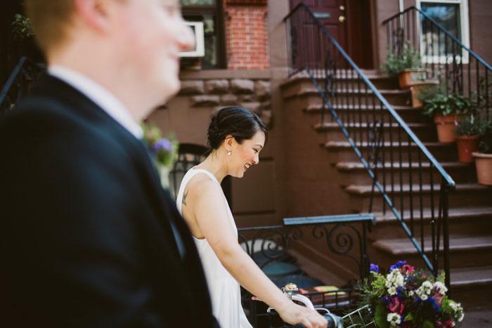 bride walking down street wheeling bike