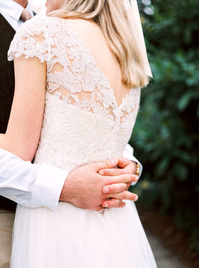 groom's hands clasped around bride's waist