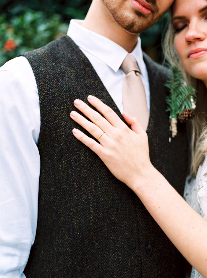 close-up of bride's hand on groom's chest