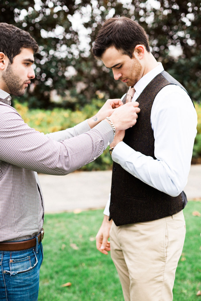 groomsman helping groom get ready