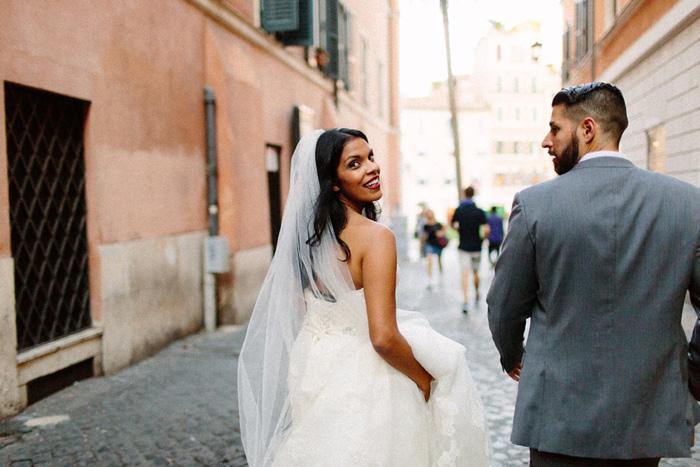 bride looking behind her shoulder as she walks down street
