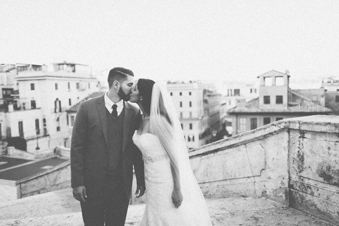 bride and groom kissing on steps in Rome