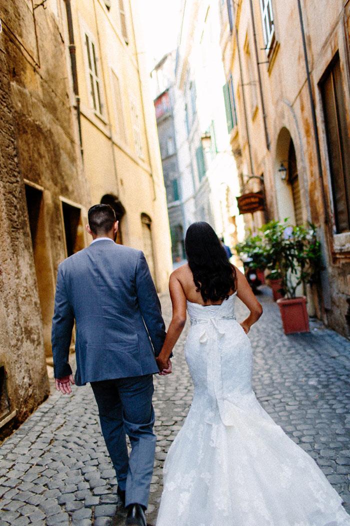 bride and groom walking down Roman alleyway