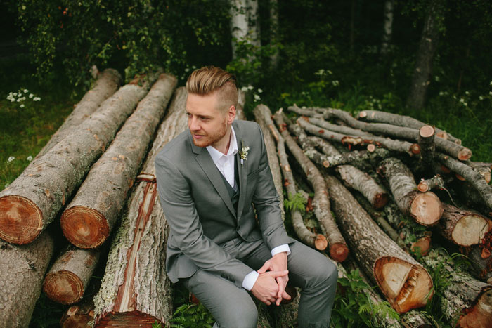 groom sitting on logs