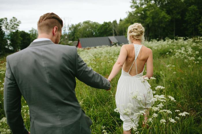 bride and groom walking through meadow