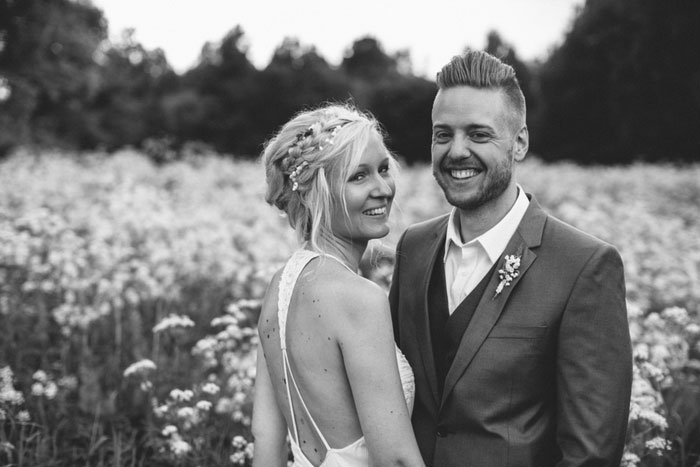 bride and groom smiling in meadow