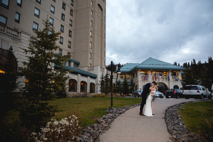 bride and groom kissing in front of hotel
