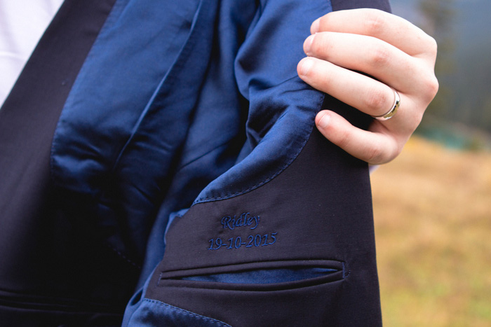 groom showing off custom embroidery inside suit jacket