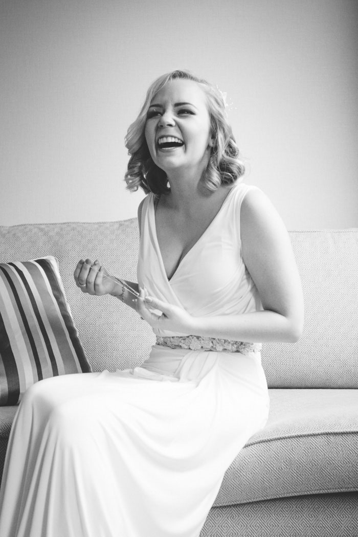 bride sitting on couch laughing