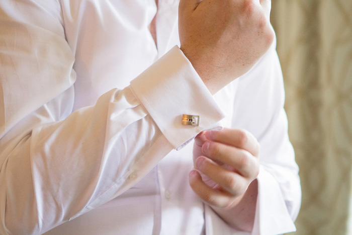 groom adjusting cuff links