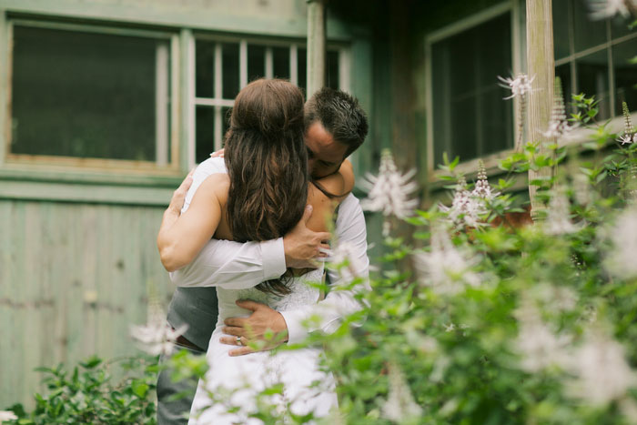bride and groom hugging outside cottage