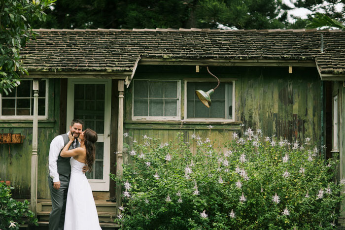 bride kissing groom in front of cottage