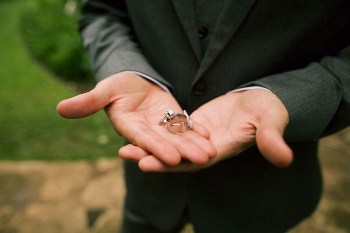 close-up of groom holding rings