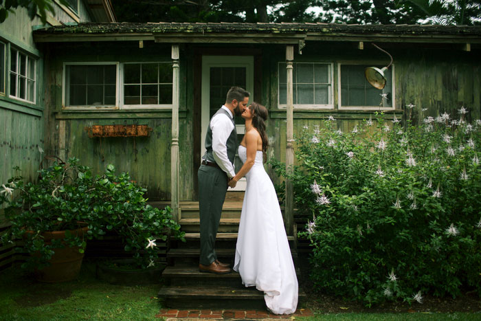 bride and groom kissing outside cottage