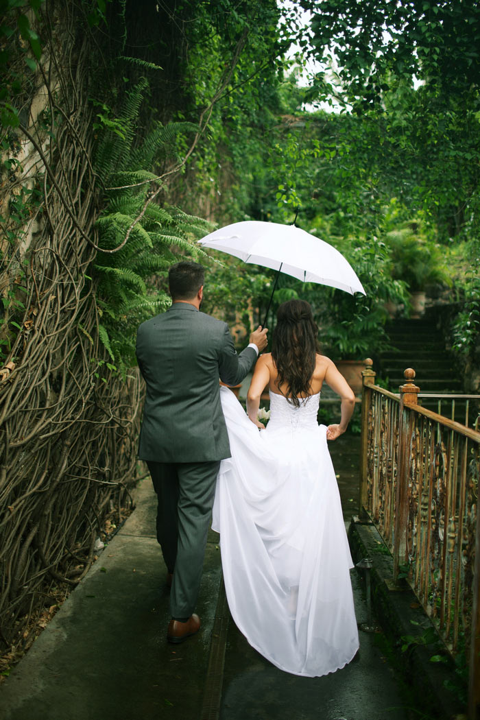 bride and groom walking under umbrella
