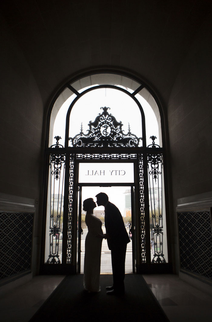 bride and groom kissing in city hall doorway