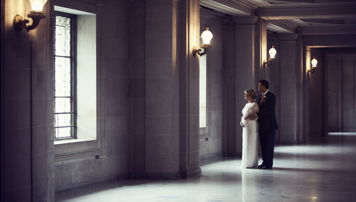 bride and groom portrait looking out window
