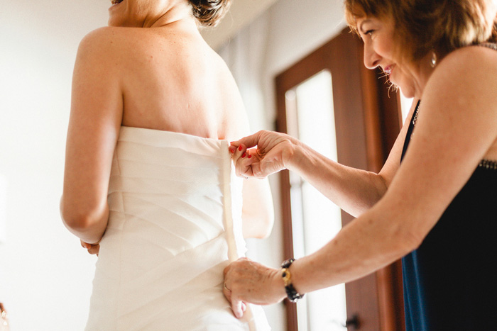 bride getting her dress zipped up