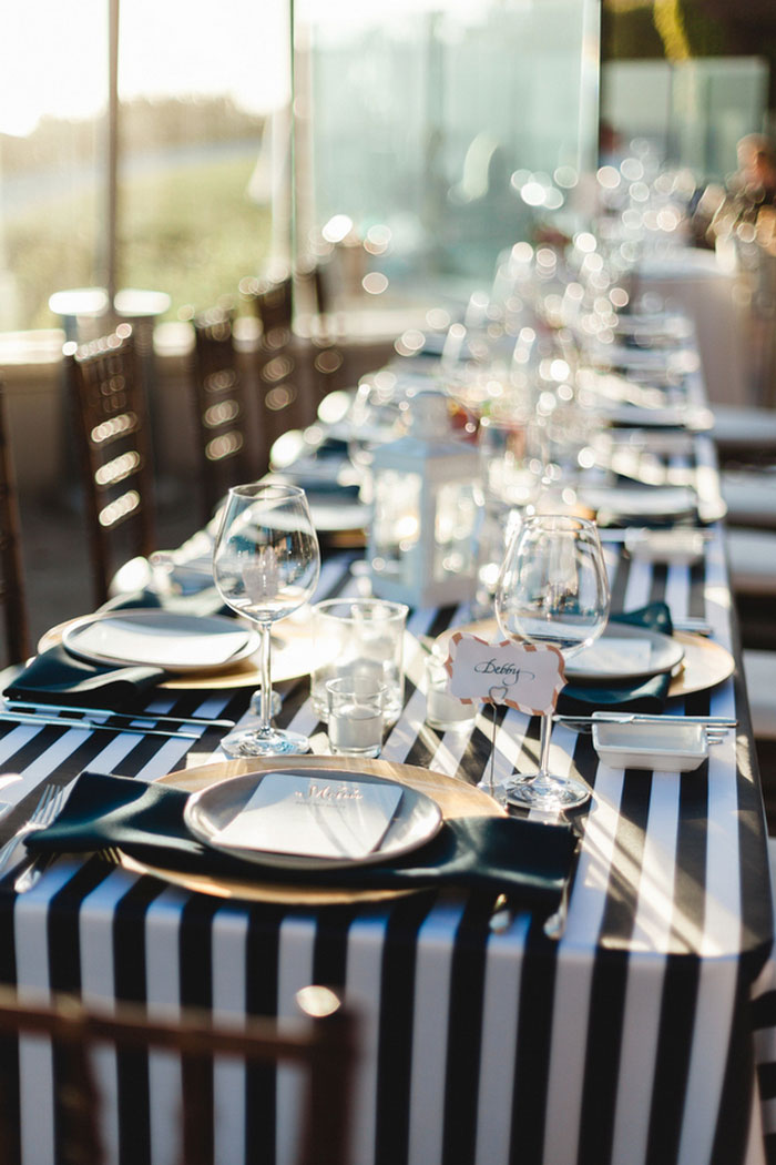 wedding table setting with black and white striped tablecloth