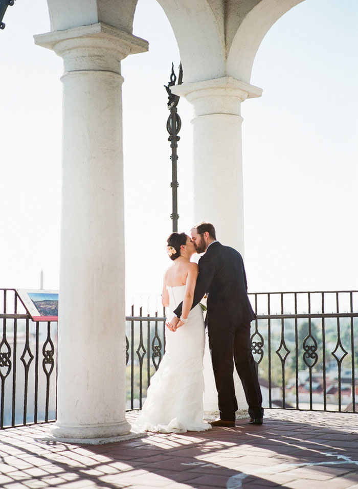 bride and groom kissing on terrace