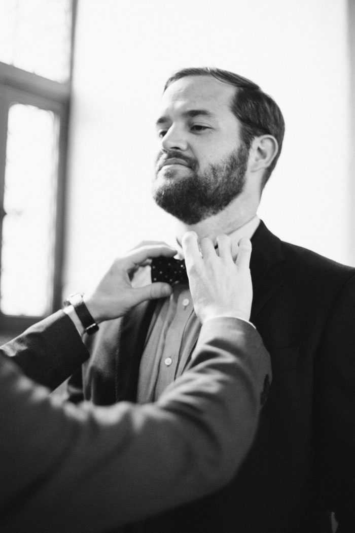 groom having bow tie adjusted