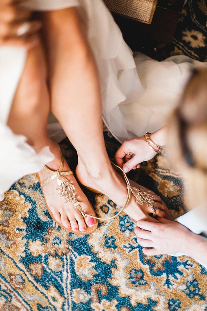 bride getting her shoes put on