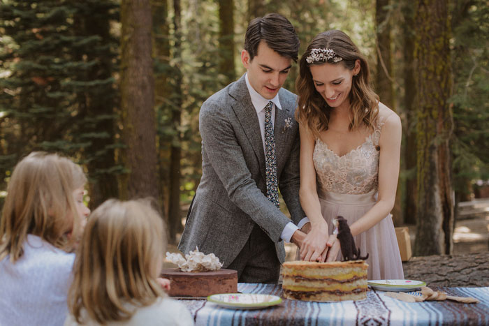 bride and groom cutting cake in the woods