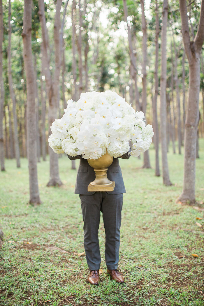 groom holding huge floral arrangement
