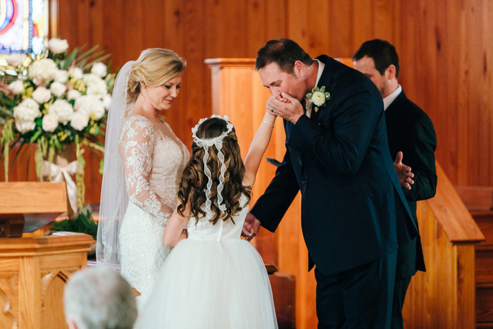 groom kissing flower girl's hand
